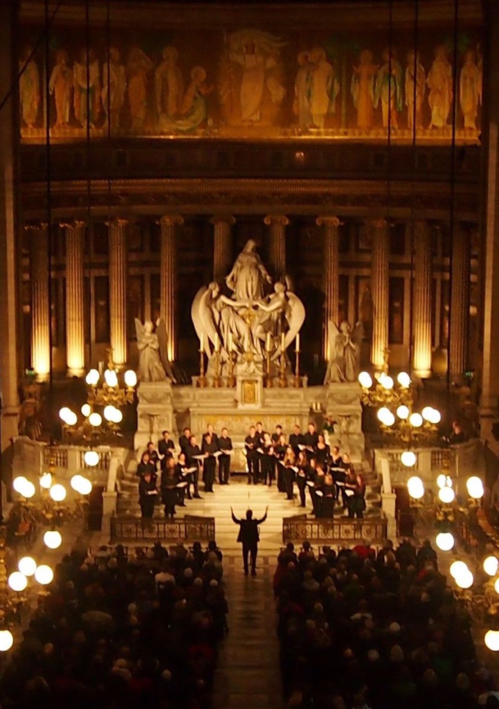 Silas Wollston conducting a choir by candlelight in a Paris chuch
